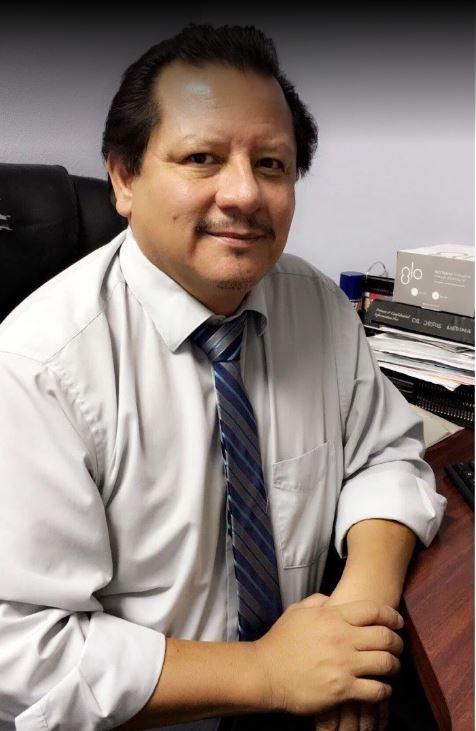 Dr Jesus Medina Las Vegas dentist sitting at his desk