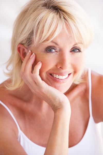 Smiling woman illustrating porcelain veneer's effect on your smile