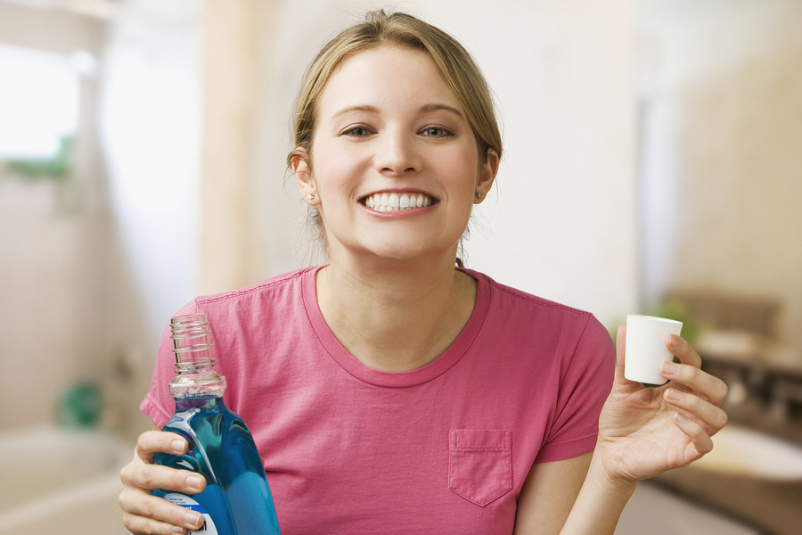 Picture of woman holding mouthwash completing oral home care