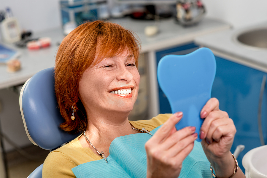 Smiling senior woman with new dental implants sitting in the dental office and looking at the mirror