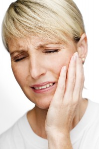 blond young woman with tooth pain holding hand to her face