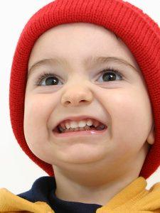 Boy in red hat grinding his teeth