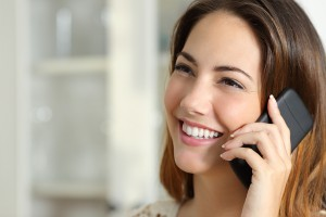 woman with beautiful teeth smiling and talking on cell phone