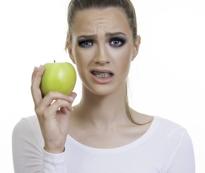 unhappy girl wearing metal braces and holding an apple she can't eat