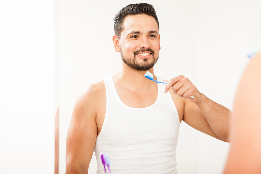 Portrait of a handsome young Hispanic man brushing his teeth