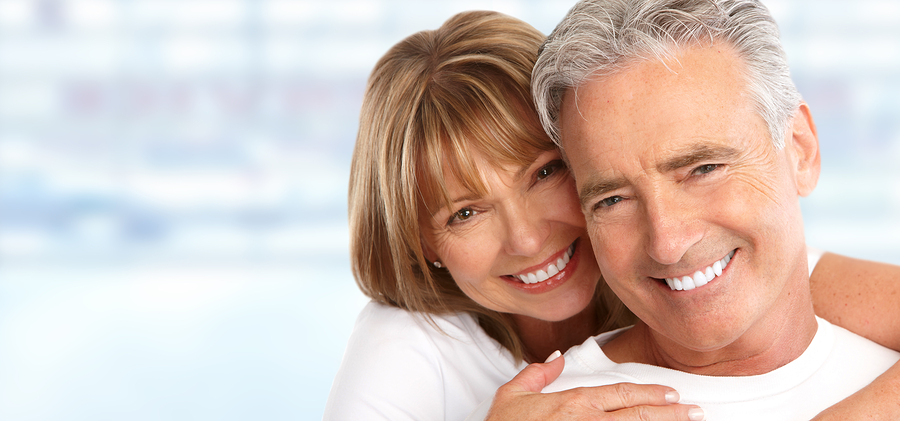 Happy Loving couple after cosmetic dental treatment showing healthy white smiles