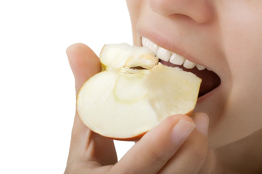 close-up of beautiful teeth a girl biting an apple