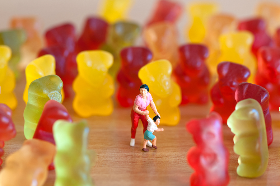 Gummy bear invasion mother and son among large gummy bears symbolizing foods bad for your teeth