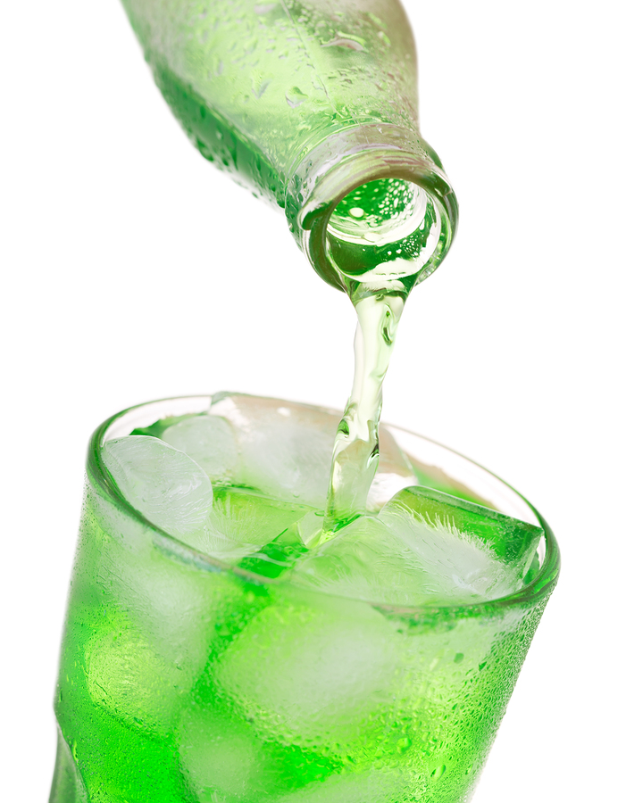 pouring green soda into glass with ice from bottle symbolizing junk food bad for your teeth