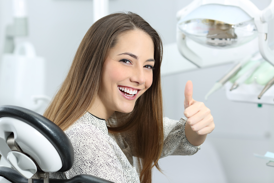 Patient with perfect white teeth and smile satisfied after dental treatment in a dentist office with medical equipment