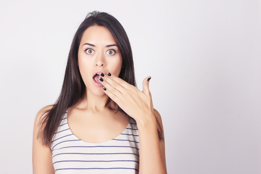 young woman acting surprised and hiding gap in her teeth with her hand