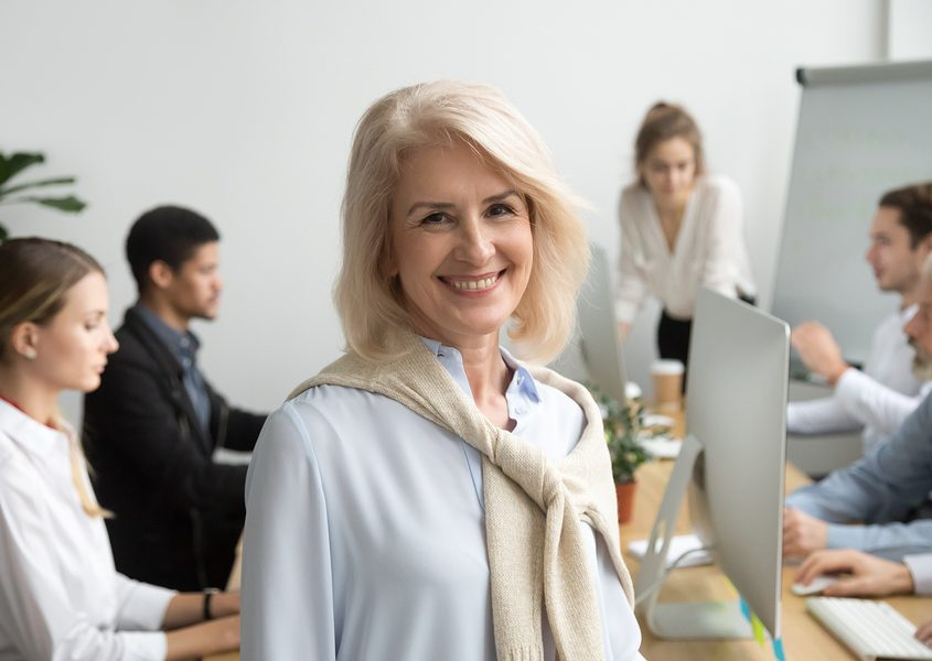 smiling mature woman with beautiful new dental implants smiling in an office environment