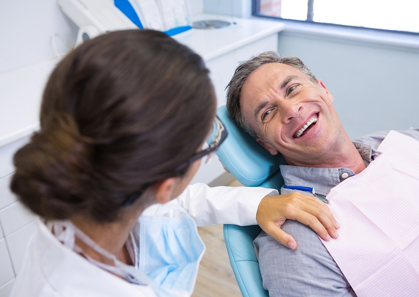 Happy dental patient sitting on chair while looking at dentist in Las Vegas