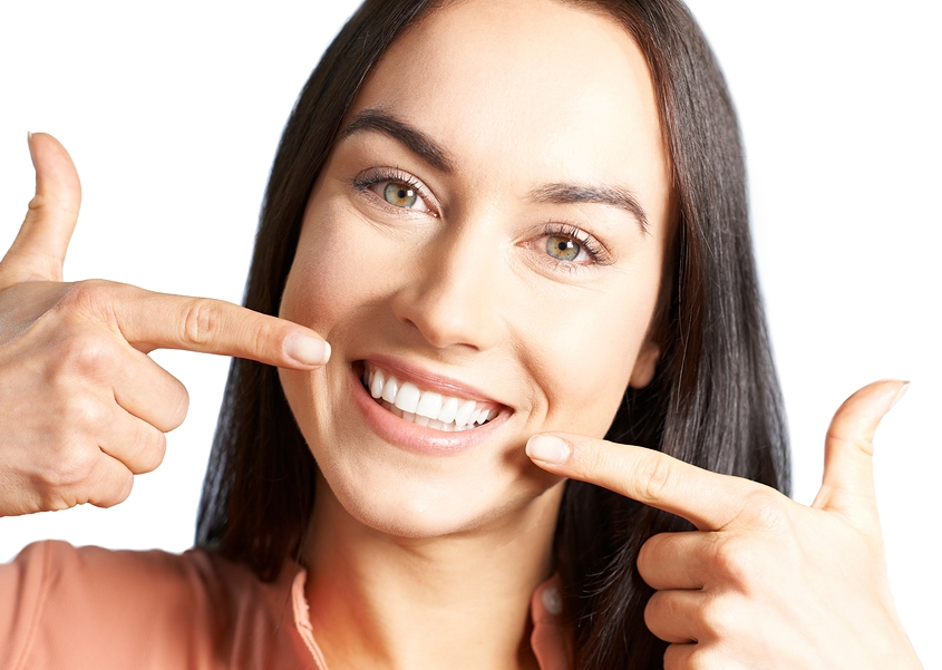 woman after dentist appointment pointing to clean white teeth and beautiful smile