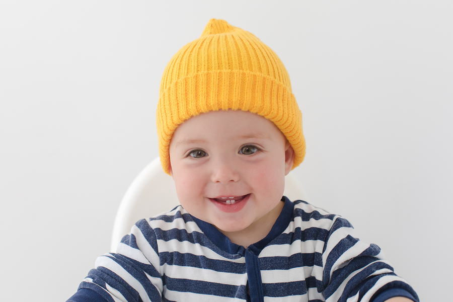 Kid in a yellow hat with two first teeth. Baby with two milk teeth smiling