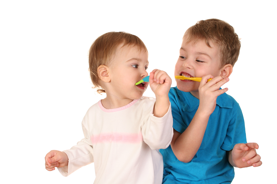 young boy and girl brushing their teeth together