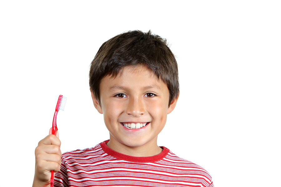 Smiling boy with red toothbrush demostrating good tooth brushing habits for kdis