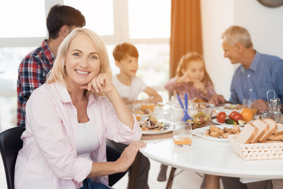 Woman smiling at family dinner table showing her new dental implants
