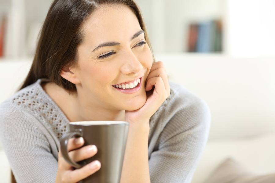 happy woman holding cup of coffee on sofa considering teeth whitening