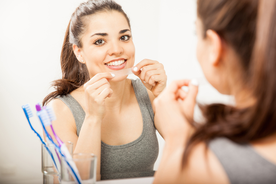 Portrait of a happy Hispanic young woman using a whitening strip on her teeth and smiling