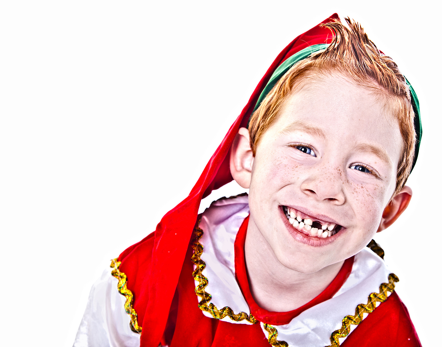 Young boy with missin front tooth smiling in a Christmas Elf costume