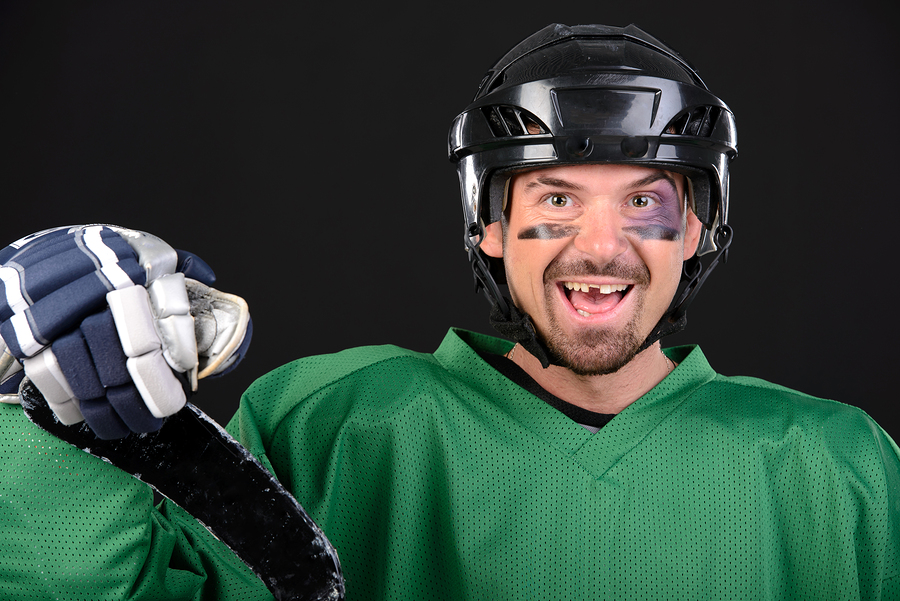 smiling hockey player with tooth loss missing front tooth