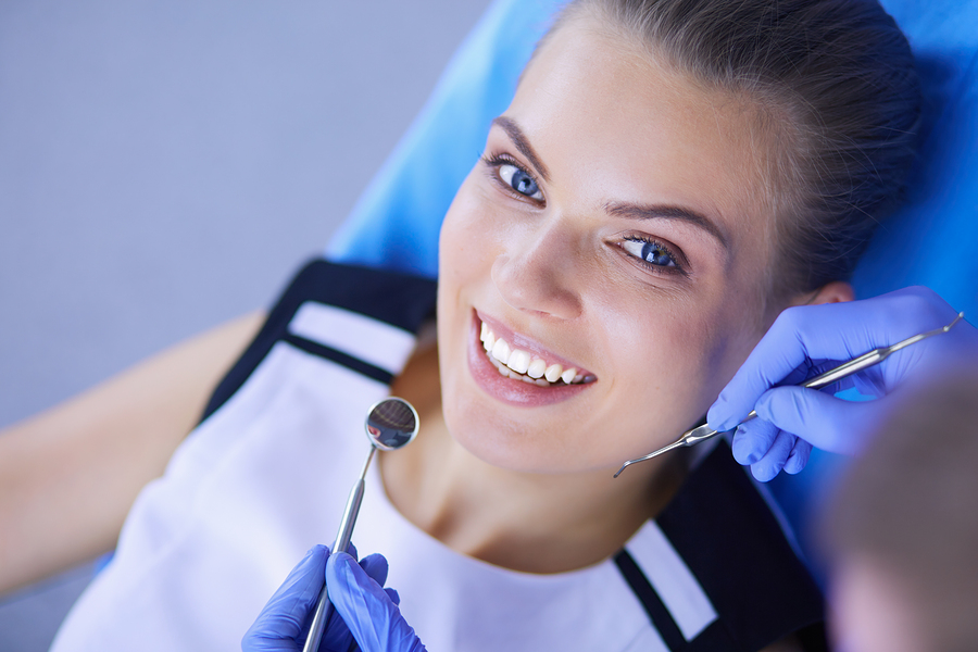 Pretty young dental patient in chair during exam of her healthy gums and teeth